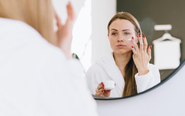 Woman applying moisturizer to her skin.