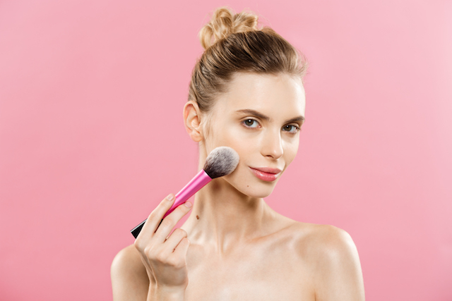 Woman applying makeup with a brush, with smooth skin.