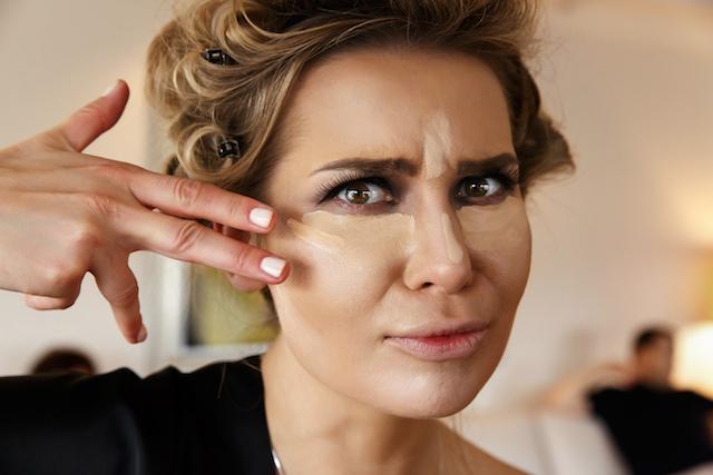 woman putting on concealer under eyes.