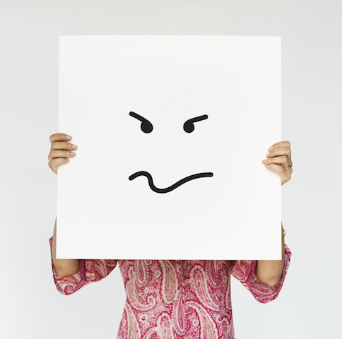 Woman holding up an angry face drawing in front of her face.