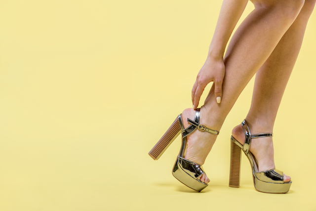 woman with high heels reaching toward the strap to adjust them.