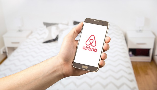 person holding mobile phone with airbnb app.