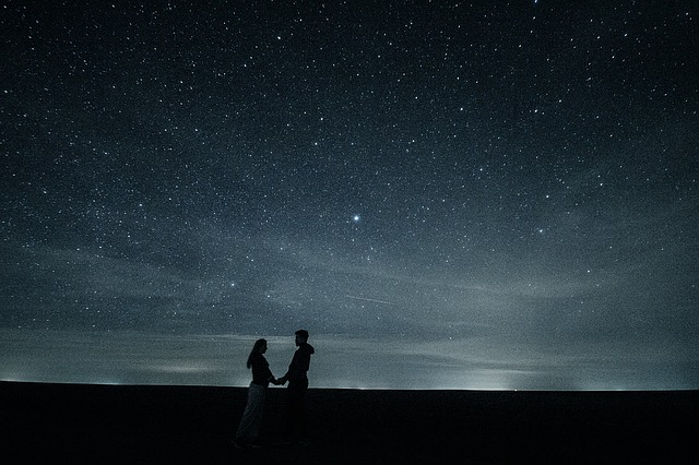 Couple holding hands under the stars.
