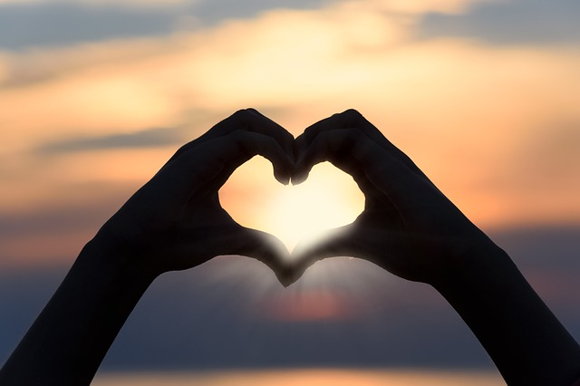 Hands together making a heart in front of a sunrise.