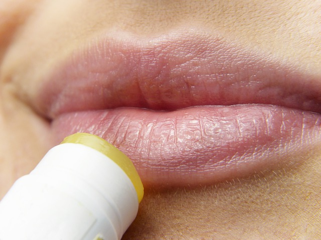 woman applying lip balm to her lips.