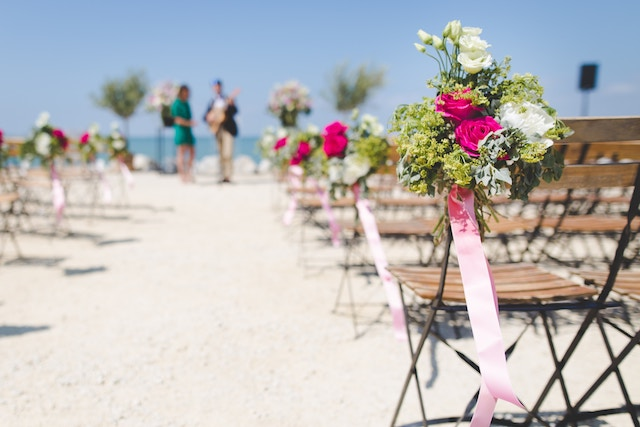 Flowers and chairs set up for a beach wedding.