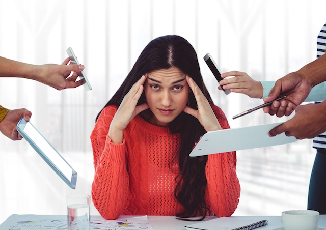 woman holding head, stressed sitting in an office.