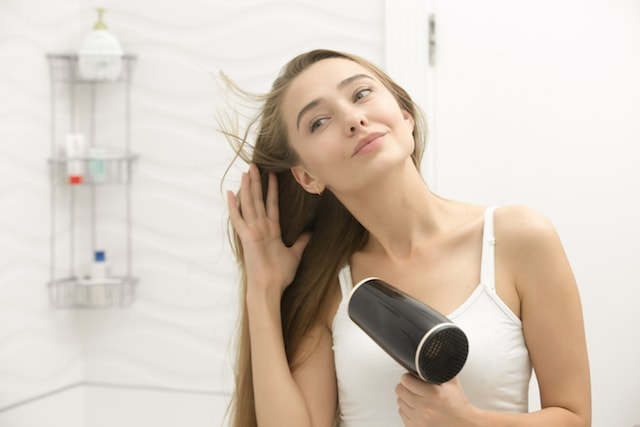 woman using a hair dryer.