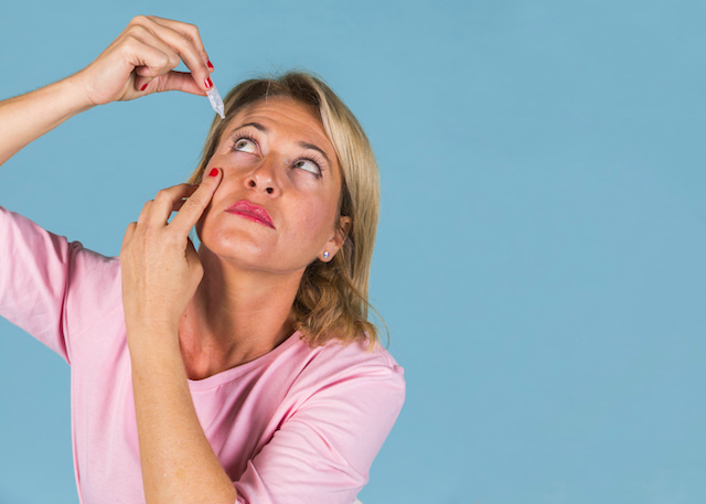 woman putting in eye drops.