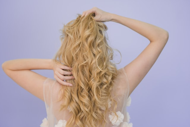 woman holding her hair, photo from the back view.