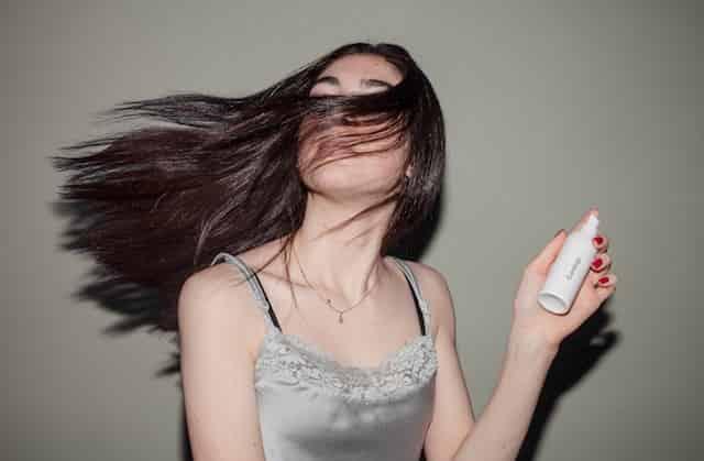 girl spinning head holding hair treatment.