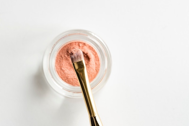 A jar of cream eyeshadow with makeup brush.