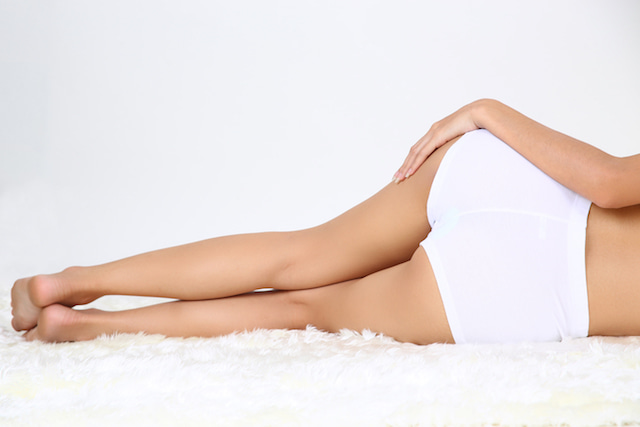 the legs and behind of a woman lying on a mat, showing smooth skin from dry brushing.