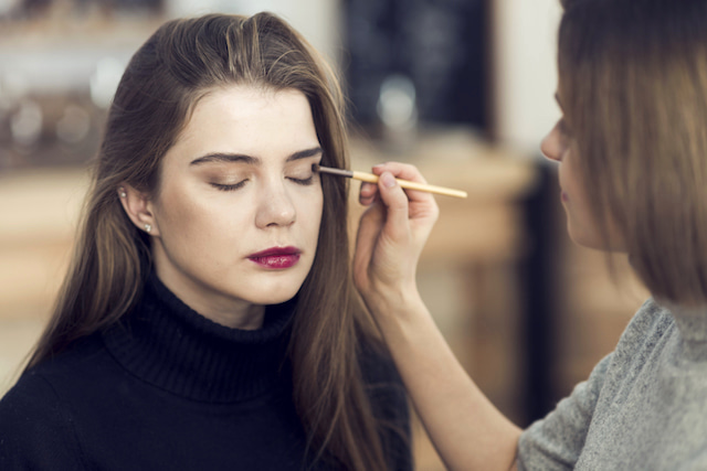 woman having eye makeup applied to lid over concealer.