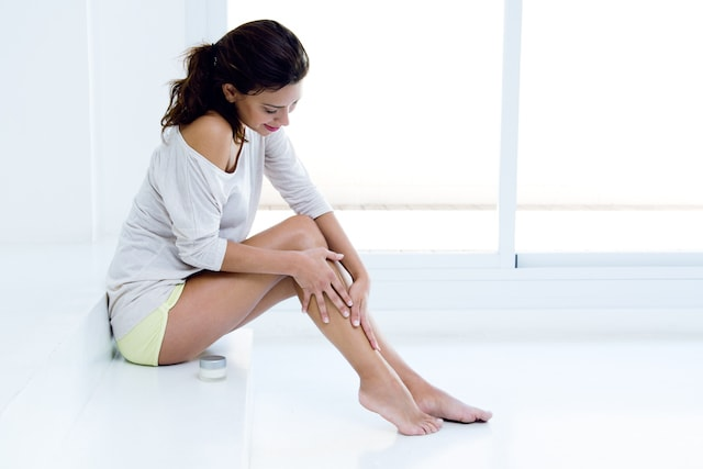 woman applying moisturizer to her legs.