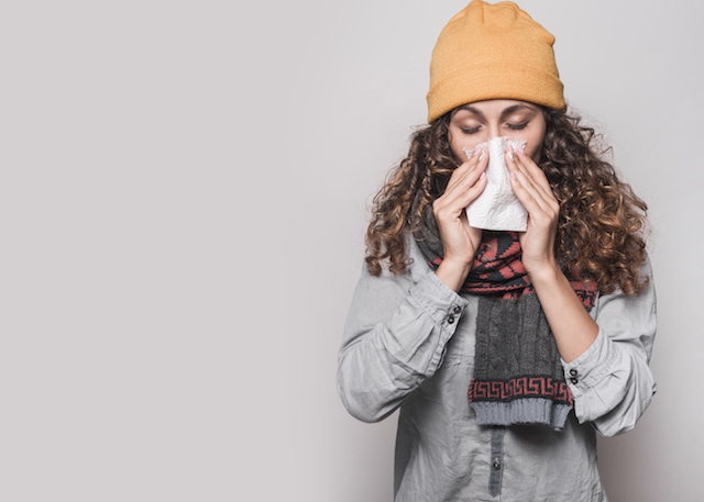 a woman sneezing wearing fall clothes.