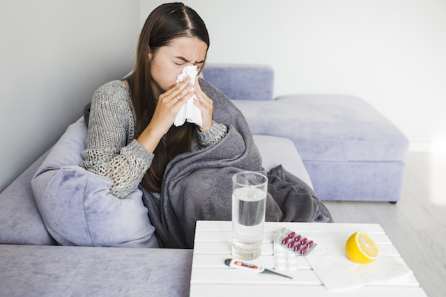 woman sneezing with different home remedies for her sinus infection.