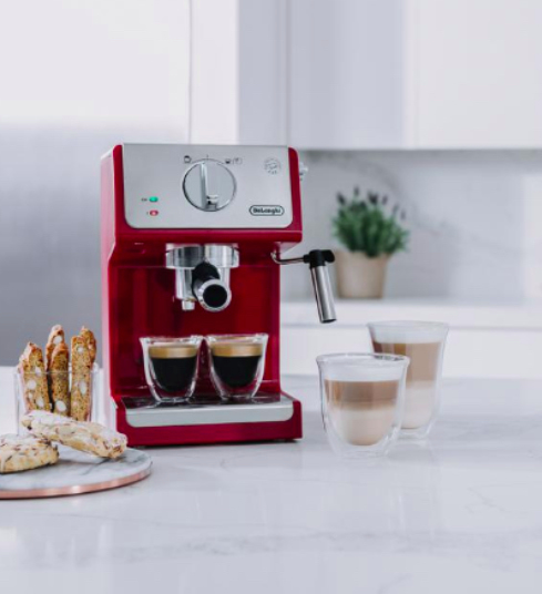 a coffeemaker with ready made coffee and biscuits in a kitchen.