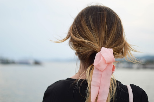 pink bow in a woman's hair.