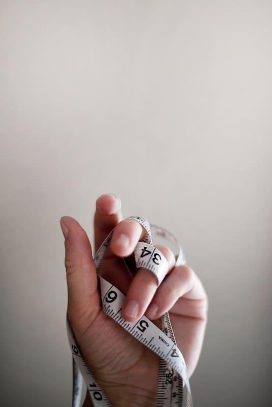 Mano sujetando una cinta métrica