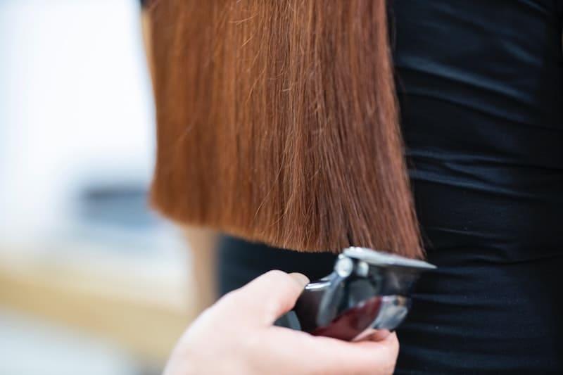 Mujer cortándole el pelo a otra mujer