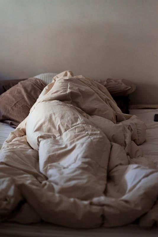 Mujer tumbada en la cama tapada hasta arriba